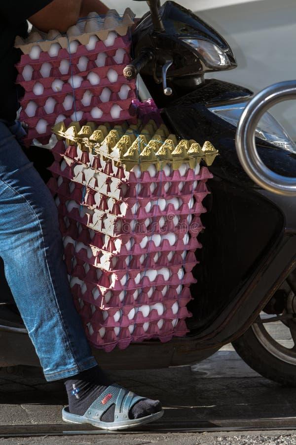 Schließen Sie oben von einem Bündel Eiern in den Karikaturkästen, die vor dem Fahrer an einem Roller sitzen stockfotografie