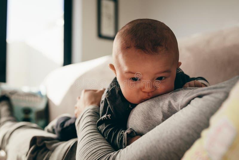Schließen Sie oben von einem Baby, das auf ihrer Mutter liegt stockfotografie
