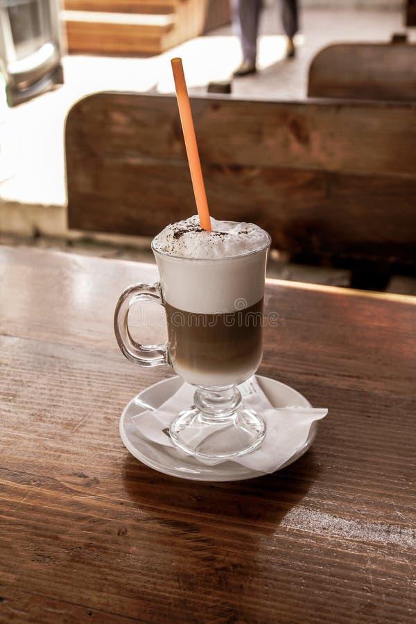 Schließen Sie oben von einem Café Latte mit einem Stroh auf einem Holztisch stockfotografie