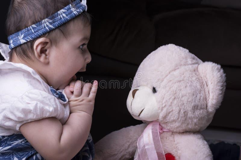 Schließen Sie oben von einem entzückenden überraschten Baby, das mit Teddybären b spielt lizenzfreie stockbilder
