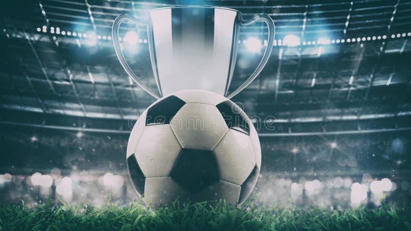 Schließen Sie oben von einem Fußball mit Trophäe in der Mitte des Stadions, das durch die Scheinwerfer belichtet wird lizenzfreie stockbilder