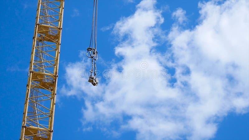 Schließen Sie oben von einem gelben und grünen Kranboom mit Hauptblock und vom Kranbalken gegen einen klaren blauen Himmel Turmba lizenzfreie stockfotografie