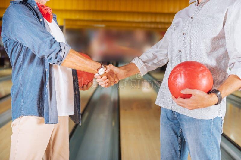 Schließen Sie oben von einem Händedruck in einem Bowlingspielverein lizenzfreies stockfoto