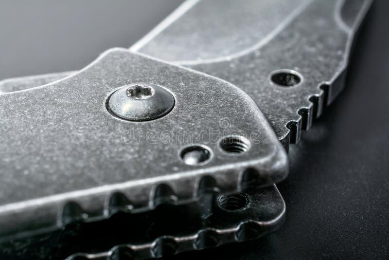 Schließen Sie oben von einem halben offenen schwarzen faltenden Messer auf dunklem Boden stockfoto