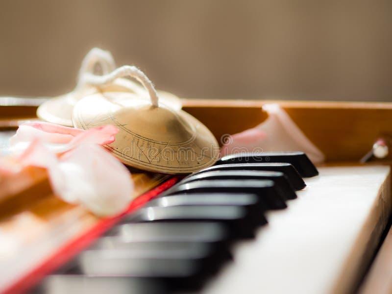 Schließen Sie oben von einem Harmonium mit Glocken und den Blumenblättern lizenzfreie stockfotografie