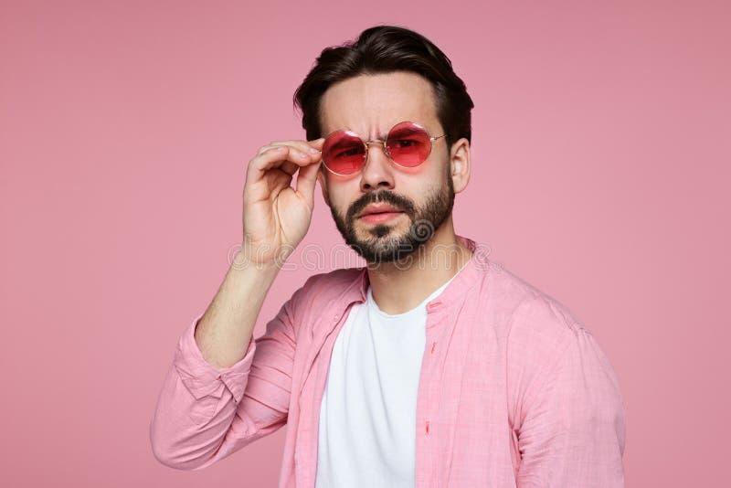 Schließen Sie oben von einem jungen ernsten Hippie-Mann in der Sonnenbrille und im stilvollen rosa Hemd und die Kamera betrachten stockfotografie