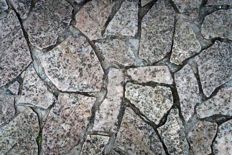 Schließen Sie oben von einem kalten und nass Steinweg Steinwegbeschaffenheit, Hintergrund mit gebrochenem Steinmaterial Alter dun lizenzfreie stockfotografie