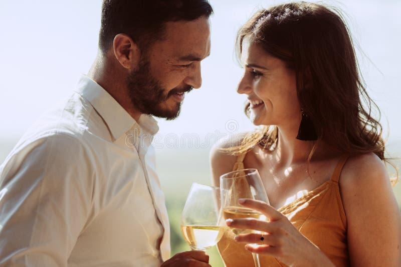 Schließen Sie oben von einem lächelnden Paar, das Weingläser zusammenhält stockbilder