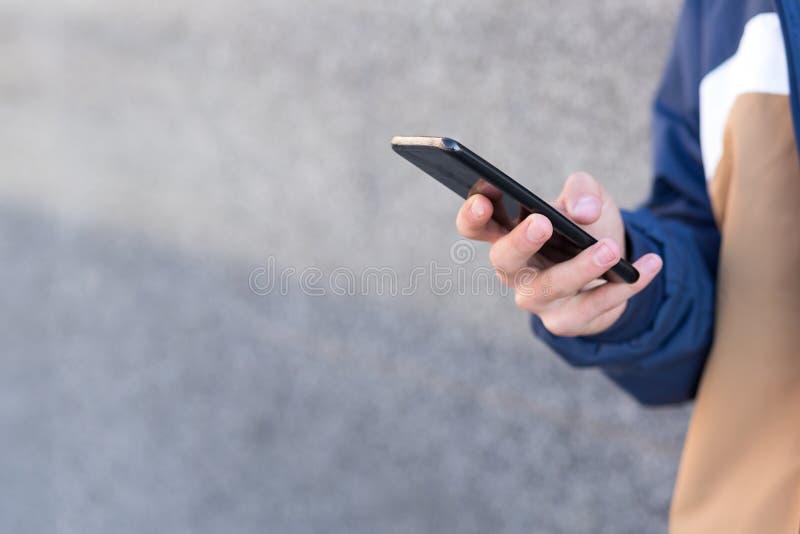 Schließen Sie oben von einem Mann unter Verwendung seines Telefons draußen lizenzfreie stockfotos