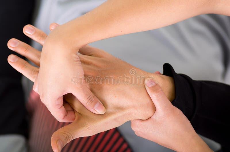 Schließen Sie oben von einem Massagephysiotherapeuten, der Handmassage eines männlichen Athleten, im Hintergrund des Ärztlichen D stockbilder