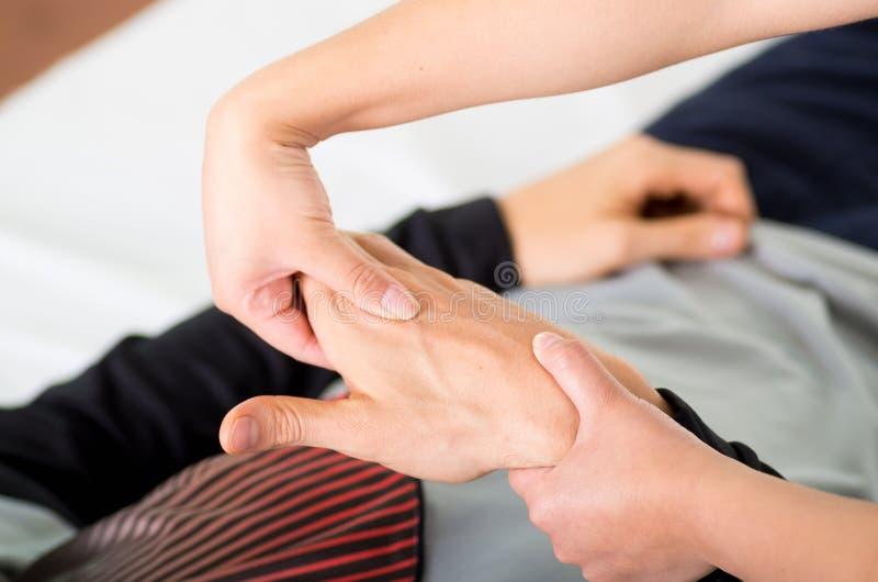 Schließen Sie oben von einem Massagephysiotherapeuten, der Handmassage eines männlichen Athleten, im Hintergrund des Ärztlichen D stockfotografie