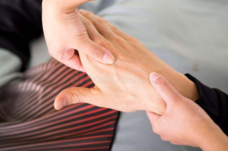 Schließen Sie oben von einem Massagephysiotherapeuten, der Handmassage eines männlichen Athleten, im Hintergrund des Ärztlichen D lizenzfreie stockbilder