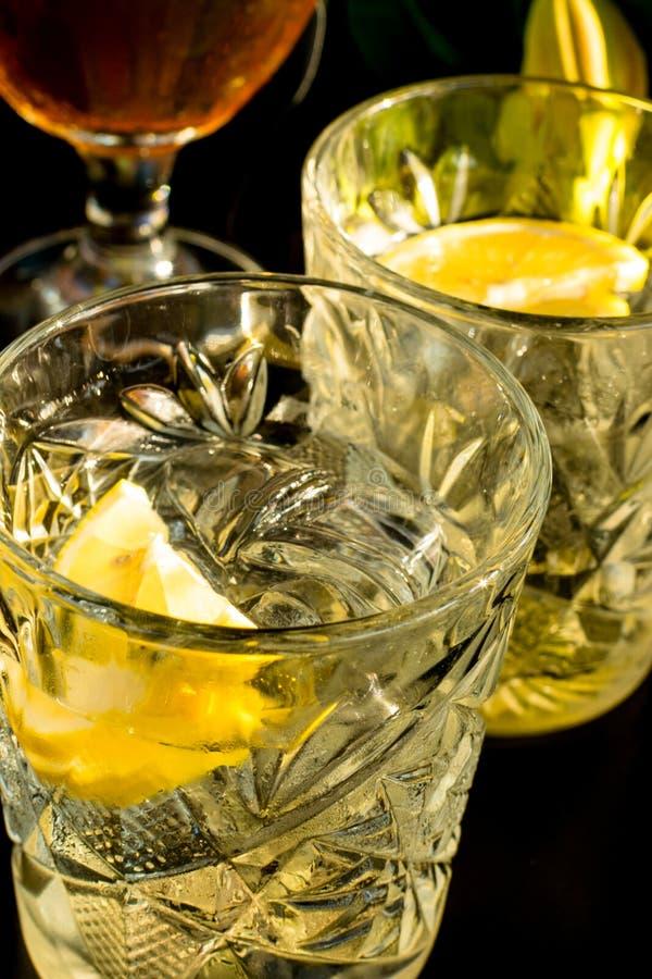 Schließen Sie oben von einem nassen Glas Kaltlichtbier mit Schaum und Wermut Martini-Alkoholcocktail mit gelben Zitronenscheiben- lizenzfreie stockfotografie