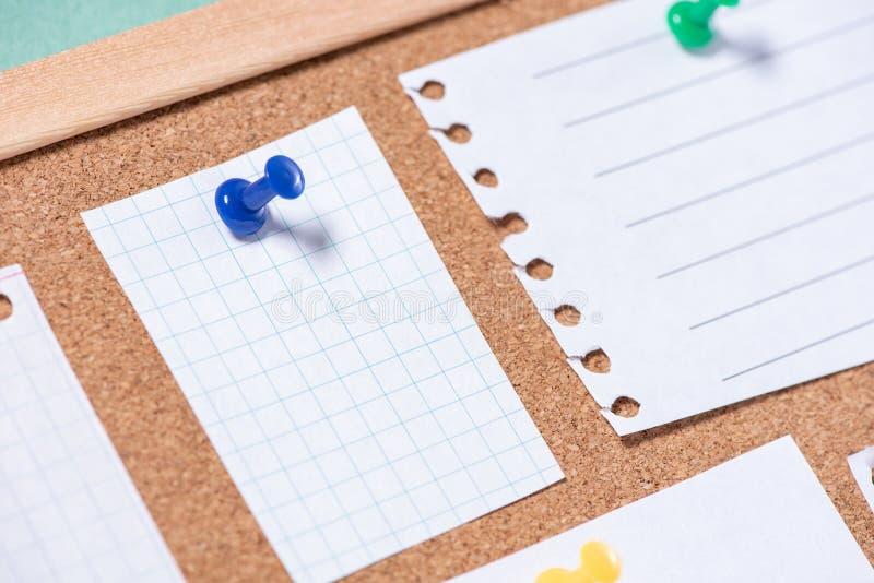 Schließen Sie oben von einem Papierblatt, das durch einen Knopf auf einem corkboard für Anmerkungen befestigt wird lizenzfreies stockbild