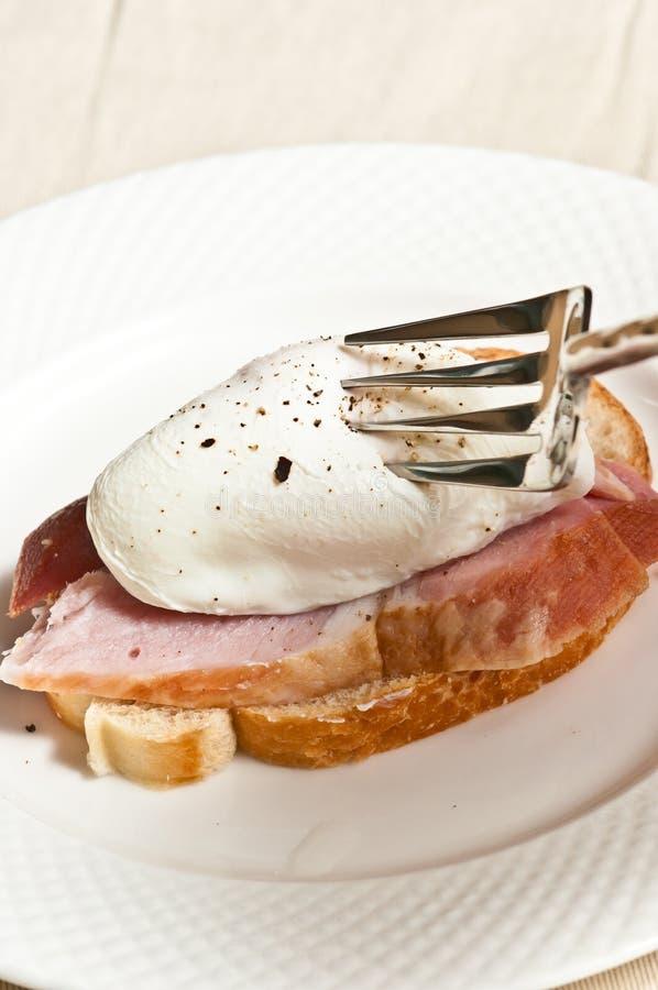 Schließen Sie oben von einem poschierten Ei auf einer Scheibe des Schinkens auf weißem Toast lizenzfreie stockfotos