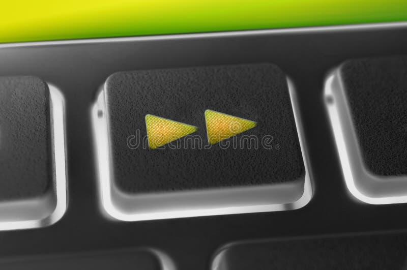 Schließen Sie oben von einem schwarzen Knopf des schnellen Vorlaufs einer schwarzen Fernbedienung mit Hintergrundbeleuchtung stockfotografie