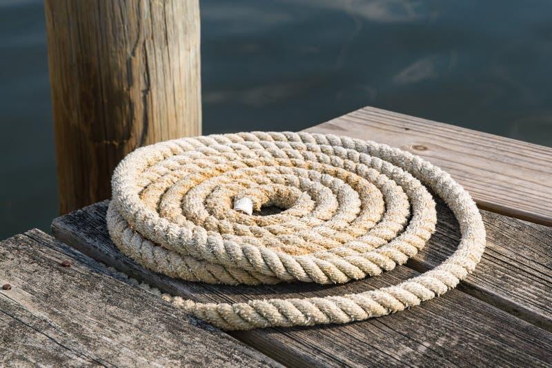 Schließen Sie oben von einem Seeseil Colied auf einem hölzernen Pier lizenzfreie stockfotografie