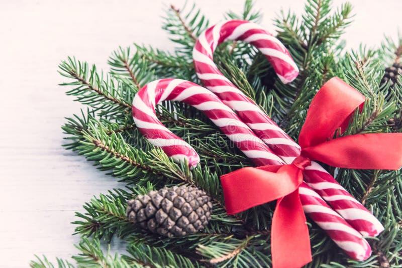 Schließen Sie oben von einem Tannenbaum und von den Süßigkeitskegeln, die mit einem roten Bogen über einem alten weißen hölzernen lizenzfreies stockfoto