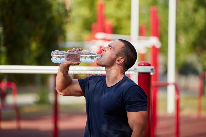Schließen Sie oben von einem Trinkwasser des Mannes von einer Flasche draußen stockfotografie