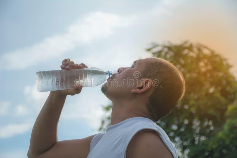 Schließen Sie oben von einem Trinkwasser des Mannes von einer Flasche nach Übung lizenzfreies stockbild