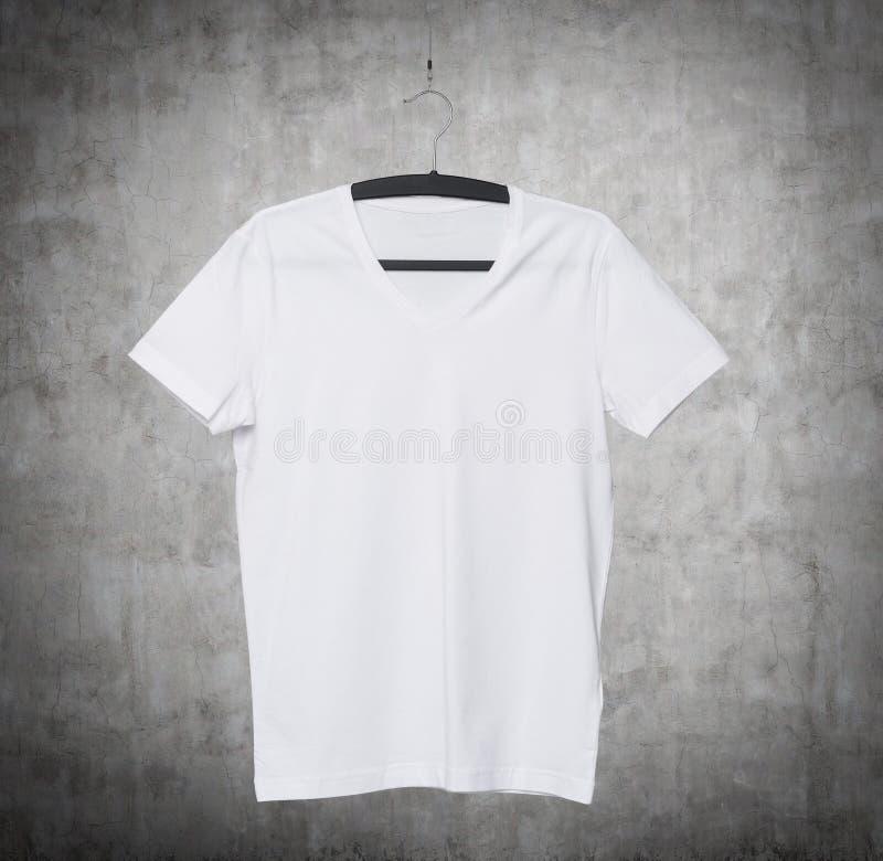 Schließen Sie oben von einem V-Form weißen T-Shirt auf Kleiderbügel lizenzfreie stockfotos