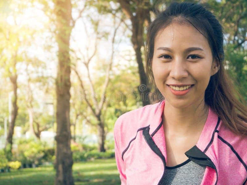 Schließen Sie oben von einer glücklichen jungen asiatischen Frau, die ihren Körper aufwärmt, indem Sie ihren Körper vor Morgenübu stockfotos