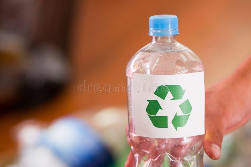 Schließen Sie oben von einer Hand, die eine Plastikflasche mit einem Druckzeichen der Wiederverwertung in der Front hält, bereite lizenzfreies stockfoto