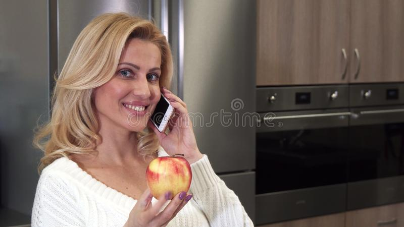 Schließen Sie oben von einer herrlichen netten Frau, die am Telefon spricht, das einen Apfel hält lizenzfreie stockfotos