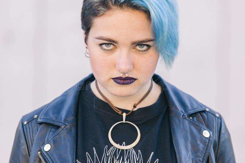 Schließen Sie oben von einer jugendlich Punkfrau mit einem Nasenpiercing, gefärbt blaues ha lizenzfreie stockfotos