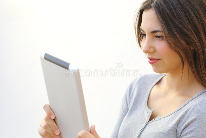 Schließen Sie oben von einer jungen Frau, die draußen einen Tablettenleser liest stockbild