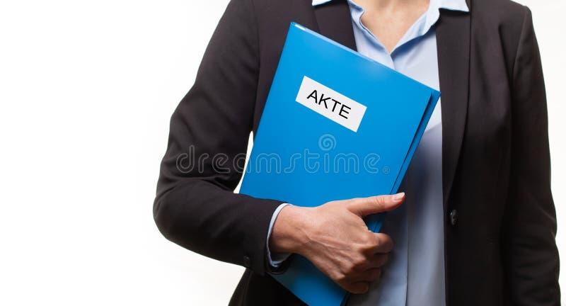 Schließen Sie oben von einer jungen Frau in einem Anzug, der eine Datei mit einem deutschen Text hält: DATEI stockfoto