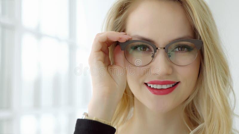 Schließen Sie oben von einer jungen Schönheit mit Gläsern am Fenster und dem Betrachten der Kamera stockbild