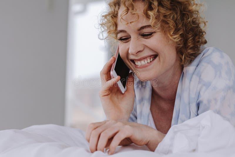 Schließen Sie oben von einer lächelnden Frau, die über dem Handy spricht, der auf b liegt stockbild