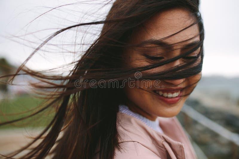 Schließen Sie oben von einer lächelnden Frau mit ihrem Haarfliegen auf ihrem Gesicht stockfoto