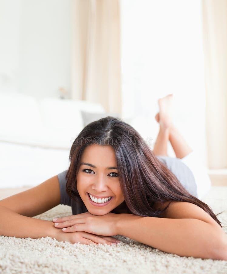 Schließen Sie oben von einer reizend Frau, die auf einem Teppich liegt stockbilder