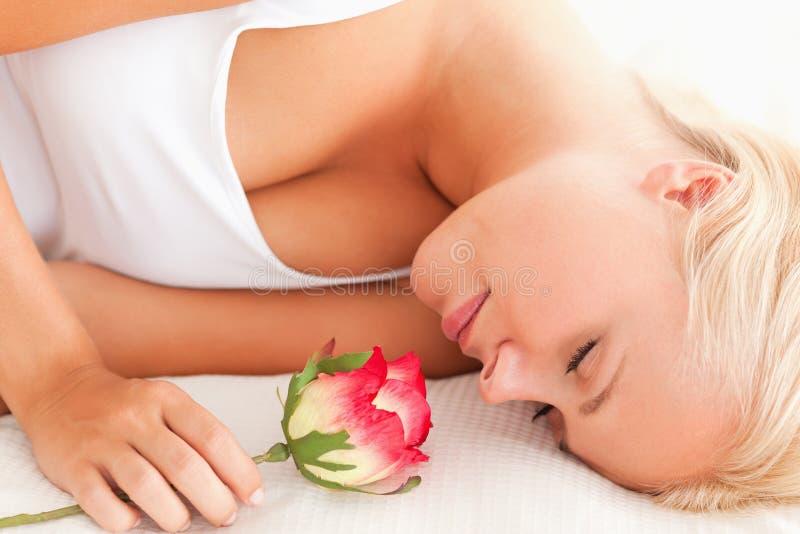 Schließen Sie oben von einer ruhigen Frau mit einer Blume stockfotos