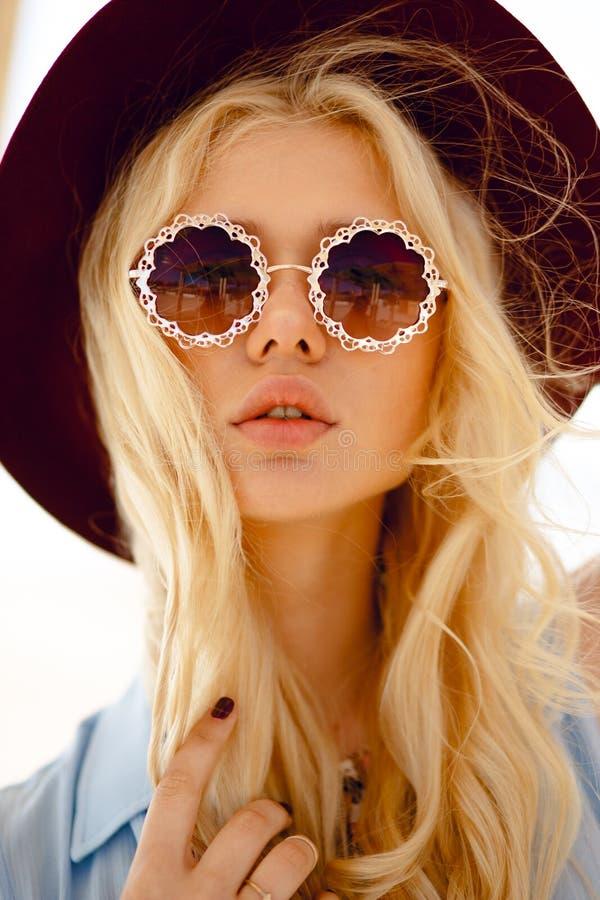 Schlie?en Sie oben von einer sinnlichen Blondine mit runder Blumensonnenbrille, gro?e Lippen, gewelltes Haar und Burgunder-Hut un lizenzfreie stockfotografie