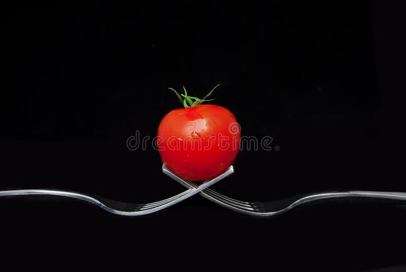 Schließen Sie oben von einer Tomate auf 2 Gabeln stockbilder