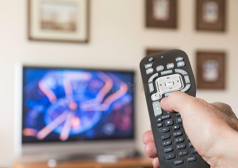 Schließen Sie oben von Fernsehapparat, der mit Fernsehen Fernsteuerungs ist lizenzfreies stockbild
