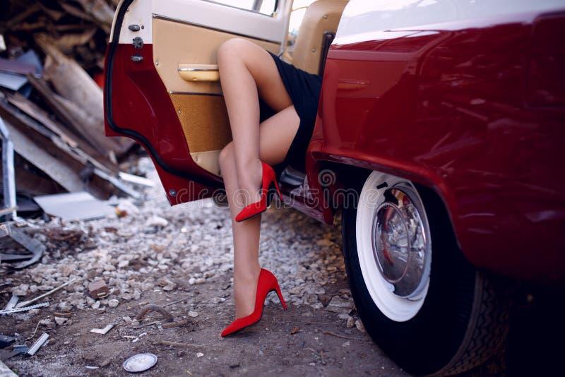 Schließen Sie oben von Frauenbeinen in den roten Schuhfersen, die nach innen auf rotem Auto der Weinlese auf Eisendumphintergrund stockbild