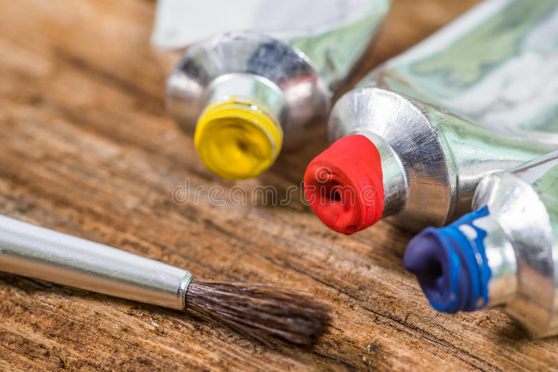 Schließen Sie oben von Gelbem, rot, blau, Temperafarbe mit Pinsel auf hölzerner Beschaffenheit lizenzfreie stockfotos