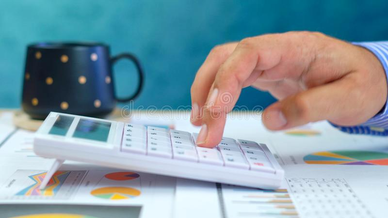 Schließen Sie oben von Geschäftsmann ` s Händen, die auf Taschenrechner hinzufügen lizenzfreie stockfotos