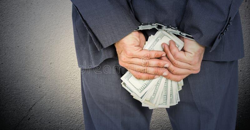 Schließen Sie oben von Geschäftsmann ` s Händen hinten zurück mit Geld und den Handschellen gegen weiße Wand stockfotografie