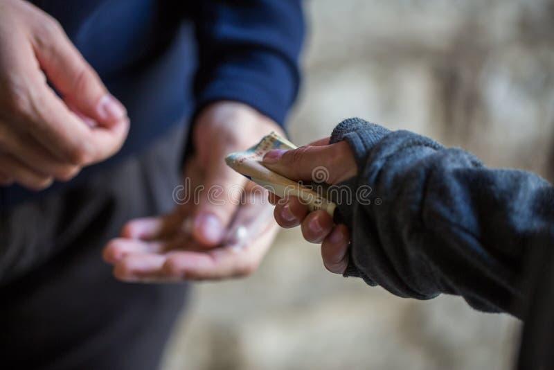 Schließen Sie oben von kaufender Dosis des Süchtigen vom Drogenhändler lizenzfreies stockbild