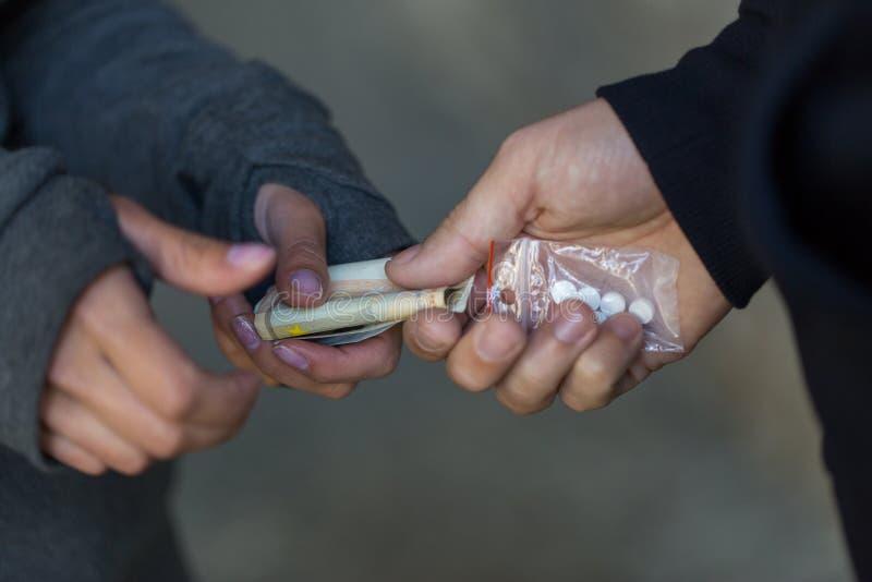 Schließen Sie oben von kaufender Dosis des Süchtigen vom Drogenhändler stockbilder