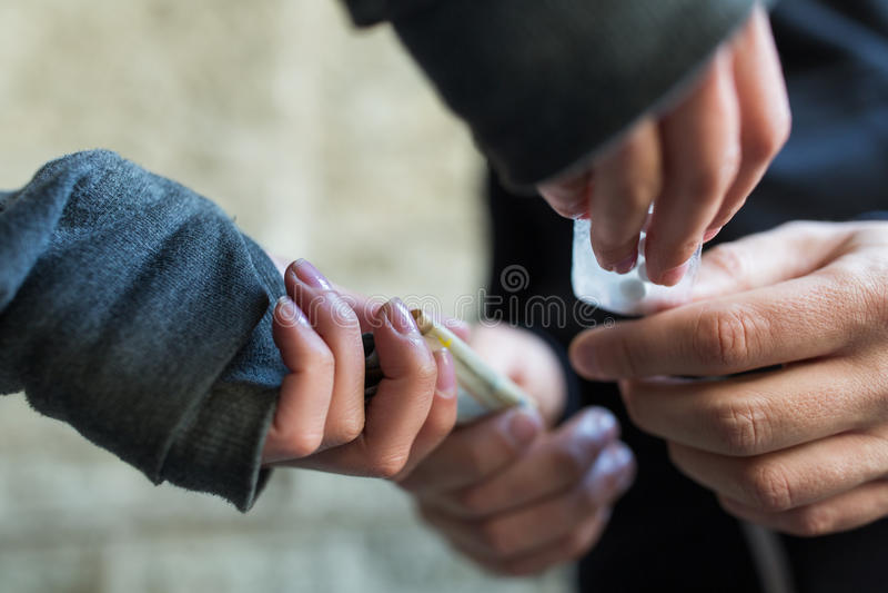 Schließen Sie oben von kaufender Dosis des Süchtigen vom Drogenhändler lizenzfreie stockfotografie