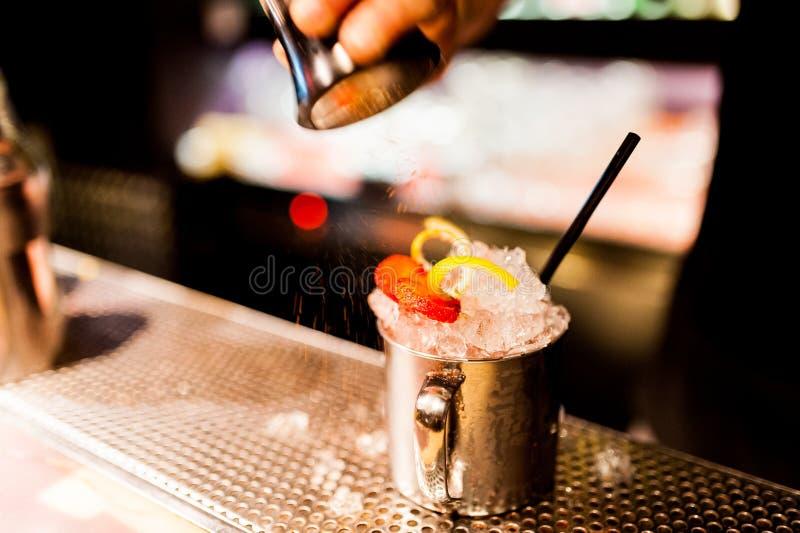 Schließen Sie oben von Kellnerhandströmendem choco Pulver auf dem Cocktailzinn, das mit Eis und Erdbeere innerhalb einer Bar nach lizenzfreie stockfotos