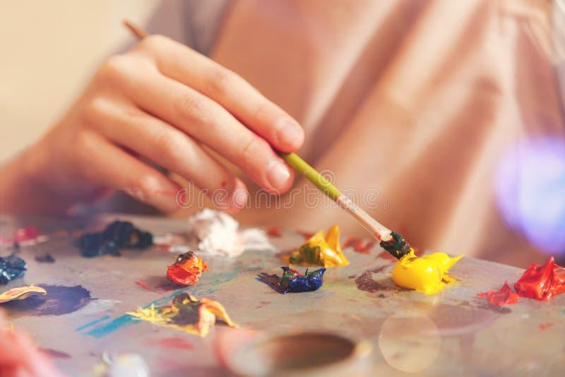Schließen Sie oben von Kindermischenden Ölfarben auf Palette stockbilder