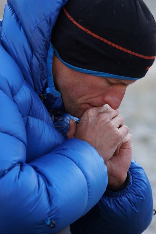 Schließen Sie oben von konzentriert und nachdenklicher Bergsteiger in der starken Abstiegjacke verlor im Gedanken stockbilder