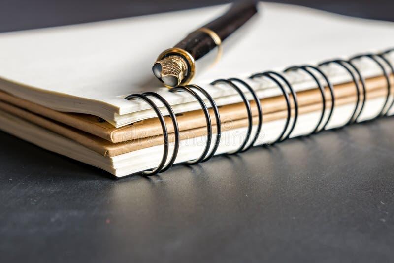 Schließen Sie oben von leerem Kraftpapier-Notizbuch und vom schwarzen Stift auf schwarzem Hintergrund lizenzfreie stockbilder